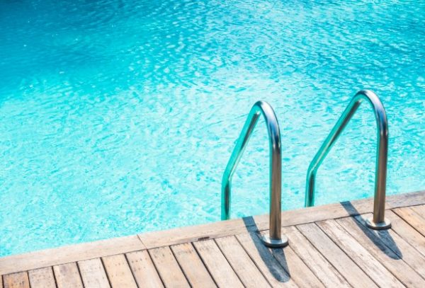 borde de una piscina con escalera lateral.